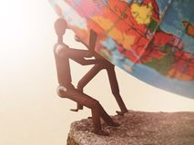 Metal figures of people trying to hold the globe. Toned royalty free stock photos