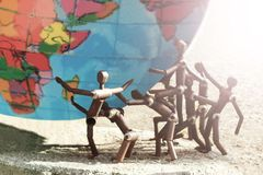 Metal figures of people trying to hold the globe. Toned stock images