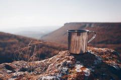Metal filiżanka na skale w halnych lasowych jesień kolorach, zamyka up, copyspace Piękny krajobraz Obraz Stock