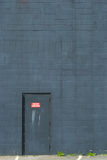 Metal fire door set into a blue-grey brick wall Stock Images