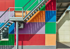 Metal fire escape or emergency exit on multicolored wall of building, abstract urban background Royalty Free Stock Photos