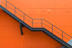 Metal fire escape or emergency exit on Orange Wall of Buliding Stock Photos