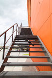 Metal fire escape or emergency exit on Orange Wall of Buliding Stock Image