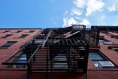 Brooklyn, NY -Metal fire escape stairs on exterior of brick building royalty free stock images