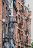 Metal fire escape stairs hanging from side of old brick apartment building Royalty Free Stock Photography