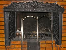 Metal fireplace with iron grate in masonry Royalty Free Stock Images