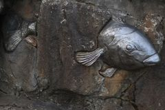 Metal fish through a cemented wall. Metal fish sculpture silver color through a cemented wall for display Stock Images
