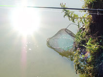 Metal fishing cage lowered into the water and the reflection of the sun in the water. The photo was taken in direct sunlight Stock Image