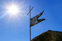 Metal flag on the top of Montalcino Fortress tower against blue Stock Photos
