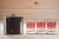 Metal flask for alcoholic drinks and three glasses on a wooden background.  Stock Photos