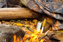 Metal flask and a knife on a log next to a raincoat of protective color campfire.  Stock Images