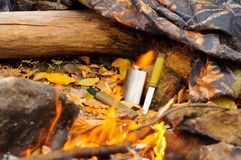 Metal flask and a knife on a log next to a raincoat of protective color campfire.  Royalty Free Stock Image