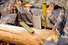 Metal flask and a knife on a log next to a raincoat of protective color. Metal flask and a knife on a log next to a raincoat of protective color Stock Photo