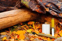 A metal flask and a knife near a log but yellow leaves next to a protective color cloak.  Royalty Free Stock Images