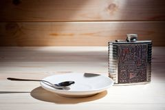 A metal flask and a saucer with a teaspoon on a wooden surface stock photography