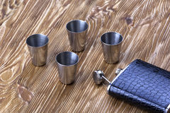 Metal flask trimmed leather and four metallic, sturdy shot glasses. Royalty Free Stock Photos