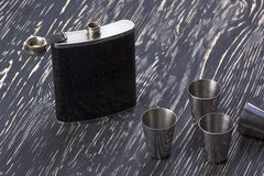 Metal flask trimmed leather and four metallic, sturdy shot glasses. Stock Photo