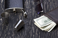 Metal flask trimmed leather, metallic  shot glasses, wallet and sunglasses Royalty Free Stock Images