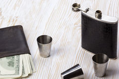 Metal flask trimmed leather, three metallic  shot glasses and wallet. Stock Photography