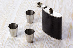 Metal flask trimmed leather and three metallic, sturdy shot glasses. Stock Photography