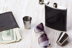 Metal flask trimmed leather, three  shot glasses, sunglasses and wallet. Stock Image