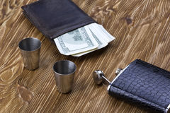 Metal flask trimmed leather, two metallic  shot glasses and wallet. Stock Photos