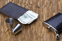 Metal flask trimmed leather, two metallic  shot glasses and wallet. Stock Images