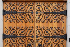 Metal floral pattern ornament on wooden doors. Wooden doors with floral pattern made of metal imprinted on wood stock photo