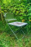 Metal folding chair. On the grass Stock Image