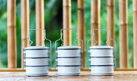 Metal food carriers  on a wooden table, a bamboo backdrop. Royalty Free Stock Image