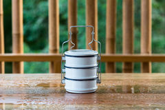 Metal food carriers  on a wooden table, a bamboo backdrop. Royalty Free Stock Images