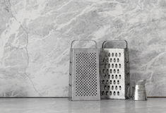 Metal food graters over marble background Royalty Free Stock Photos