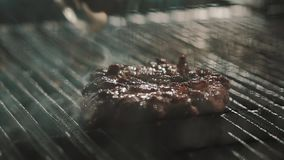 Metal forceps turns over meat cooking on hot smoking grill stock video footage