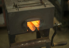 Metal forge heating steel in blacksmith shop Stock Photo