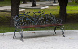 Metal forged bench in summer park Stock Image