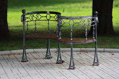 Metal forged bench in summer park Stock Photos
