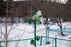 A metal forged cross with artificial flowers, on an old village cemetery. A metal forged cross with artificial flowers in the old village cemetery of the Royalty Free Stock Photography