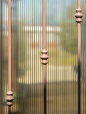 Metal forged fence and sheets of translucent brown polycarbonate. Blurred image of the summer garden behind. Royalty Free Stock Images
