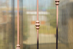 Metal forged fence and sheets of translucent brown polycarbonate. Blurred image of the summer garden behind. Royalty Free Stock Photography