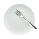 Metal fork in a ceramic plate isolated Stock Images