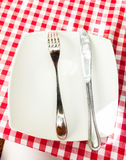 Metal fork and knife lying on white plate at checkered red cloth Stock Photo