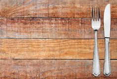 Metal fork and knife on wood plank table texture background Royalty Free Stock Images