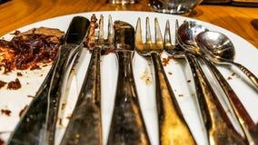Metal a forquilha, a faca e a colher com a sobremesa terminada do chocolate Fotos de Stock Royalty Free