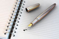 Metal fountain pen on notebook Stock Photography