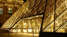 Metal Frame Glass Pyramid Outside a Museum With Yellow Lights during Nighttime Stock Photo