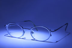 Metal Frame Glasses. Close-up and focus on the corner of metal frame glasses. Blue toned Stock Photos