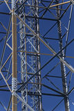 Metal frame of telecommunications tower in front of a dark blue sky Royalty Free Stock Photo