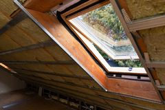 Metal frames on attic skylight window and environmentally friendly and energy efficient thermal insulation rock wool. In natural light royalty free stock photo
