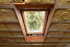 Metal frames on attic skylight window and environmentally friendly and energy efficient thermal insulation rock wool. In natural light stock image