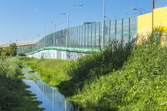 Sound-absorbing screens along the highway and the creek. Metal frames filled with glass and yellow sound-absorbing panels.Modern technology in Poland royalty free stock photography